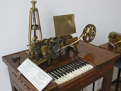Hughes telegraph, an early (1855) teleprinter built by Siemens and Halske. The centrifugal governor to achieve synchronicity with the other end can be seen clearly.