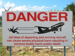 Sign warning people that standing too close to the airport fence on Maho Beach can be dangerous