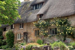 Cottage with thatched roof in Stanton, a village in the Cotswolds, England
