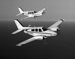 Two Baron 55s flying in formation with a 1980-built B55 nearest. E55 in background.