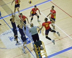 A Spanish player, #18 in red outfit, about to spike towards the Portuguese field, whose players try to block the way
