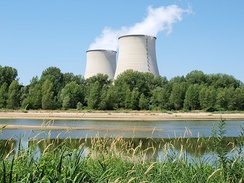Nuclear power plant in Cattenom, France four large cooling towers expelling white water vapor against a blue sky