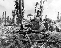 Three U.S.  Marines and their machine gun lay heavy fire on a Japanese sniper nest (July 28, 1944).