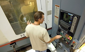 "A ""numerical controlled machining cell machinist"" monitors a B-1B aircraft part being manufactured."