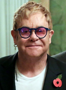 Elton wearing his remembrance poppy in 2015 commemorating those who have died while serving in the British Armed Forces