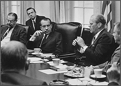 Men in suits are shown meeting in a conference room. Five men are shown, one of whom is speaking to man on his right. A sixth man is visible from behind, facing the speaker.