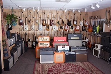 A range of guitar combo amps and guitars for sale at a music store.