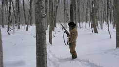An agent armed with an M14 rifle tracking someone in harsh winter conditions on the northern border.