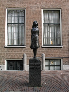 This statue in Amsterdam commemorates Anne Frank, a Jewish girl who went into hiding with her family during the Second World War. They were found and transported. Her father survived and later published her diary. (She is presumably represented by a stone at Westerbork.)