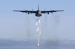 A Michigan Air National Guard C-130E dispatches its flares during a low-level training mission
