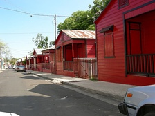 Distinctive red-and-black striped cottages at Calle 25 de Enero