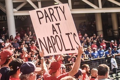 "A double-sided sign, the visible side of which states ""Party at Napoli's"""