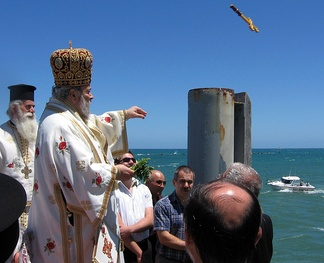 Greek Orthodox bishop at the Great Blessing of Waters on Theophany, releasing the cross off the Glenelg Jetty, South Australia, for one of the swimmers below to retrieve.