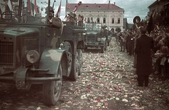 Crowds throw flowers to welcome the Hungarian troops into Kézdivásárhely