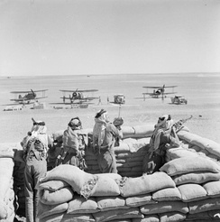 Gloster Gladiators of No. 94 Squadron RAF Detachment, guarded by Arab Legionnaires, refuel during their journey from Ismailia, Egypt, to reinforce Habbaniya