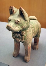 Left: a Chinese ceramic statue of a seated woman holding a bronze mirror, Eastern Han period (25–220 AD), Sichuan Provincial Museum, ChengduRight: a pottery dog found in a Han tomb wearing a decorative dog collar, indicating their domestication as pets,[182] while it is known from written sources that the emperor's imperial parks had kennels for keeping hunting dogs.[183]