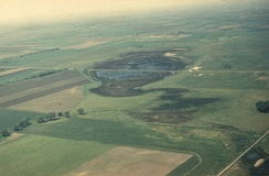 An aerial photo of a prairie pothole with a road through the center
