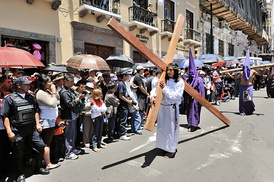 A Good Friday procession in Ecuador. The man is shown holding a cross, representing the one upon which Jesus was crucified.