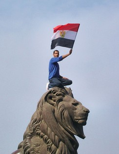 Man crouched on top of the famous Qasr al-Nil Bridge stone fish, waving the Egyptian flag