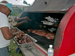 "A barrel-shaped barbecue on a trailer at a block party in Kansas City. Pans on the top shelf hold hamburgers and hot dogs that were grilled earlier when the coals were hot. The lower grill is now being used to cook pork ribs and ""drunken chicken"" slowly, typical on a worker's paid holiday – see Barbecue in the United States."