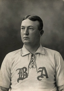 "A black-and-white photograph of a man from the chest up looking to his right, wearing a baseball uniform with the letters ""B"" and ""A""."