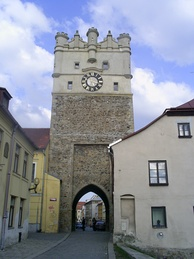View of a street of old bauildings, the largest of which is a tall clock tower with an archway