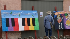 A man looking at a painting at the 23rd Annual Brownsville Latin Jazz Festival