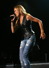 A woman in a black vest and jeans holding a microphone on a stage.