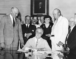President Roosevelt signs the Social Security Act into law, August 14, 1935. (Lewis at far right)