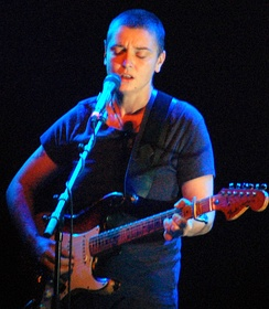 Sinéad O'Connor playing a Fender guitar with a capo