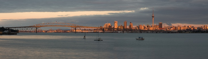The Auckland CBD skyline and Harbour Bridge at sunset.