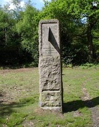 "A standing stone in a grassy field surrounded by trees. The stone contains a vertical sundial centered on 1 o'clock, and is inscribed ""HORAS NON NUMERO NISI ÆSTIVAS"" and ""SUMMER TIME ACT 1925"""