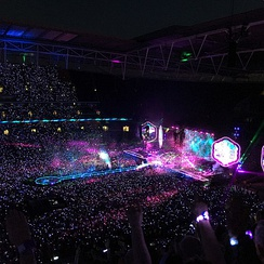 Coldplay at Wembley Stadium in 2016. Their live shows have evolved over time making them visually spectacular, which include using lasers, glowballs and Interactive LED wristbands that light-up concertgoers.