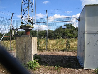 "Base feed: Radio frequency power is fed to the mast by a wire attached to it, which comes from a matching network inside the ""antenna tuning hut"" at right.  The brown ceramic insulator at the base keeps the mast isolated from the ground.  On the left there is an earthing switch and a spark gap for lightning protection."