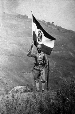 An East African Askari soldier holding the German Empire's colonial flag