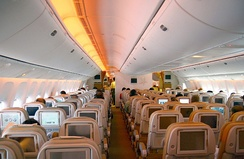 Airliner cabin. Rows of seats arranged between two aisles. Each seatback has a monitor; light shines from the sidewalls and overhead bins.