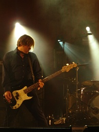 Collins is playing his bass guitar with his left hand on the fret board and right hand with fingers plucking at the strings. His head is bent to his left and down, his fair haired fringe hangs over his eyes. He wears a dark long shirt. A drum kit is beyond him, further to his left. Stage lights shine down from above.