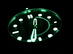 A long exposure photo of a watch in the dark. Note the appearance of the second hand as it rotates, showing that this was a 30-second exposure. The hour hand (which has only moved barely) is clear, while the minute hand is slightly blurry from a half a minute of movement.