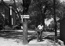 An African-American child at a segregated drinking fountain on a courthouse lawn, North Carolina, US 1938.