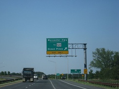 A divided highway curves to the left as the rightmost lane exits underneath an overhead green sign indicating the ramp leads to Worcester Highway and MD 589 toward Ocean Pines.