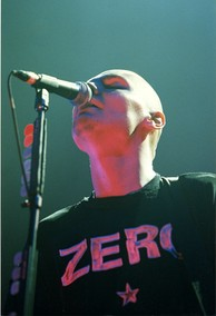 "A man with a shaved head, singing into a microphone with his eyes closed. He is wearing a black shirt with the text ""Zero"" across the front."