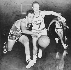 Point guards Bob Cousy (left) and Bob McNeill (right) chase after the ball. Cousy won six NBA championships with the Boston Celtics.