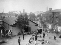 A vantage-point picture of a prison camp at the Suomenlinna Fortress in Helsinki. Around 25 Red prisoners are present in the courtyard, surrounded by a shack and a garrison building.