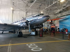 Delta Ship 41 in Historic Hangar 1, with the Stinson Reliant in the background.
