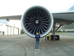 Aircraft engine, forward-facing view with a Boeing engineer in front to demonstrate the engine's size. The engine's large circular intake contains a central hub with a swirl mark, surrounded by multiple curved fan blades.