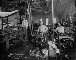 1917 press room, using a line shaft power system. At right are several small platen jobbing presses, at left, a cylinder press.