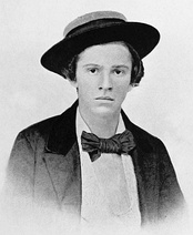 A young North American boy of the 19th century. In this black-and-white photograph, the boy looks into the camera nervously, a straw boater perched upon his head. He wears a white shirt, dark jacket and a large, dark-coloured bow tie.