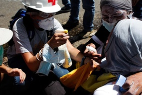 A paramedic tending to an opposition protester during the 2014 Venezuelan protests