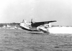 A U.S. Coast Guard PBM takes off from the water assisted by RATO.