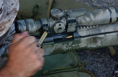 A US Marine extracts a fired cartridge casing and chambers a new round into his M40A3.